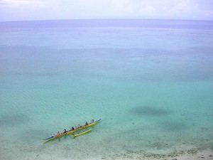 people rowing an outrigger canoe with a view of the vast pacific  behind them